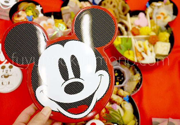 ミッキーマウスの顔が描かれた蓋とおせち料理